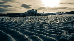 Bambrugh castle across waves of rippled sand